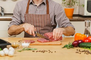 Close up caucasian young man in apron sitting at table with vegetables, cooking at home preparing meat stake from pork, beef or lamb, in light kitchen with wooden surface, full of fancy kitchenware.