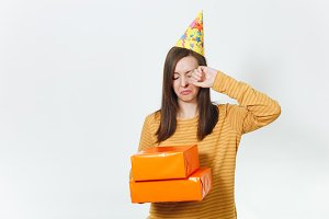 Beautiful crying upset young sad woman in yellow clothes, birthday party hat holding orange gift boxes with present, celebrating bad holiday alone on white background isolated for advertisement.