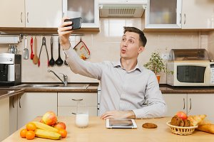 Handsome young business man in plaid shirt having breakfast, sitting at table, doing selfie on mobile phone, eating cereals with milk on light kitchen. Healthy lifestyle. Cooking at home. Prepare food