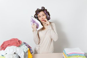 Distressed fun housewife with curlers on hair in light clothes smoking cigarette at ironing board talking on iron like mobile phone. Woman isolated on white background. Copy space for advertisement.