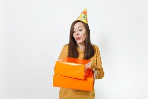 Beautiful caucasian fun young happy woman in yellow clothes, birthday party hat holding orange gift boxes with present, celebrating and enjoying holiday on white background isolated for advertisement.