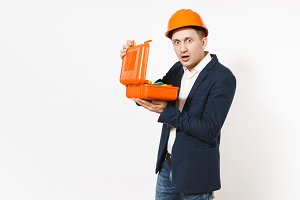 Young shocked businessman in dark suit, protective hardhat holding opened case with instruments or toolbox isolated on white background. Male worker for advertisement. Business, working concept.