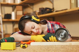 Young tired woman in plaid shirt, gray T-shirt, noise insulated headphones, yellow gloves working in carpentry workshop at wooden table place with different tools, sleeping on wood with power saw.