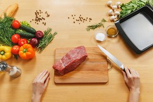 Raw meat. Fresh beef tenderloin on cutting board on wooden table with different vegetables, spices, mushrooms, baking tray, knife. Top view flatlay. Copy space for advertisement. Woman cuts with knife