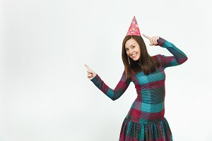 Beautiful caucasian young woman in plaid dress and birthday party hat with charming smile, celebrating holiday pointing two fingers away at copy space isolated over white background for advertisement.