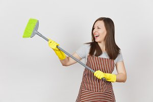 Young smiling housewife in striped apron, yellow gloves isolated on white background. Fun housekeeper woman cleaning maid holding and sweeping with broom. Copy space for advertisement Advertising area