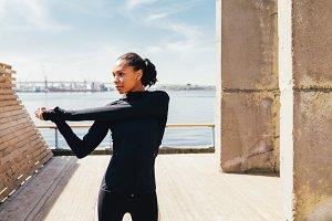 Woman in sportswear warming up hand