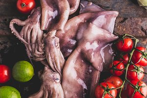 Fresh raw seafood squid calamary and ingredients on dark background. Top view