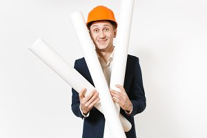 Young handsome happy businessman in dark suit, protective construction orange helmet holding blueprints plans isolated on white background. Male worker for advertisement. Business, working concept.