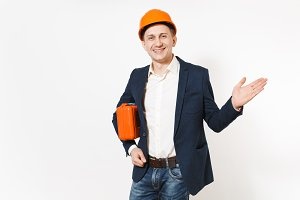 Young handsome smiling businessman in dark suit, protective hardhat holding case with instruments or toolbox and keeping hands in pockets isolated on white background. Male worker for advertisement.