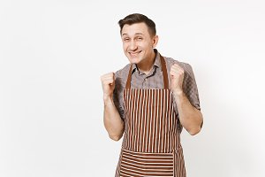 Young shy man chef or waiter in striped brown apron, shirt holds hands up hope for best isolated on white background. Male housekeeper or houseworker looking camera. Domestic worker for advertisement.