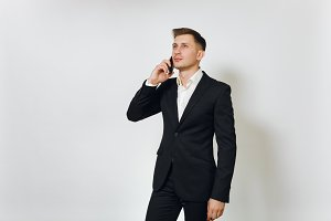Young successful handsome rich business man in black suit talking on modern mobile phone isolated on white background for advertising. Concept of money, achievement, career and wealth in 25-30 years.