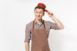 Young fun crazy happy man chef or waiter in striped brown apron, shirt holding red empty stewpan on head isolated on white background. Male housekeeper or houseworker. Kitchenware and cuisine concept.