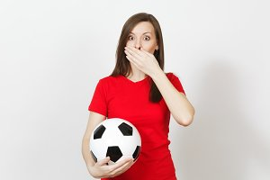 Beautiful European young woman, football fan or player in red uniform cover mouth with hand, hold soccer ball isolated on white background. Sport, play football, health, healthy lifestyle concept.