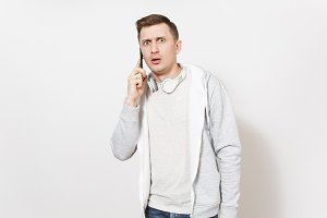Young handsome student in t-shirt and light sweatshirt with headphones around neck talks on mobile phone and looks in surprise in studio on white background. Concept of communication