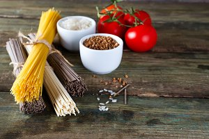 bunch of Italian spaghetti, noodles soba and sommel, bowls with buckwheat and rice with tomato on an old wooden background