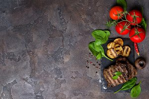 Beef steak and grilled vegetables on slate board on stone table.