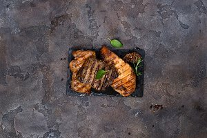 Fresh three types of grilled steak (chicken, pork, beef) on slate plate with herbs
