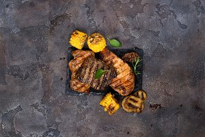 Fresh three types of grilled steak (chicken, pork, beef) on slate plate with herbs and grilled potatoes