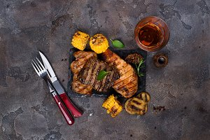 Fresh three types of grilled steak (chicken, pork, beef) on slate plate with herbs, juice and grilled potatoes