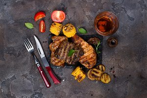 Fresh three types of grilled steak (chicken, pork, beef) on slate plate with herbs, tomato, juice and grilled potatoes