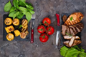 Fresh three types of grilled steak (chicken, pork, beef) on slate plate with spinach, tomato and grilled potatoes