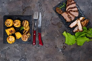 Fresh three types of grilled steak (chicken, pork, beef) on slate plate with spinach and grilled potatoes