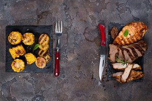 Fresh three types of grilled steak (chicken, pork, beef) on slate plate with spinach, corn grill and grilled potatoes
