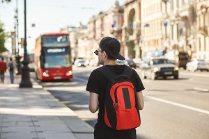 People, travel, tourism and education concept - stylish young man with backpack over london city bus on street background