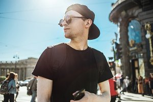 Handsome man tourist with phone. Young man standing on a street of european city. Navigation, travel concept