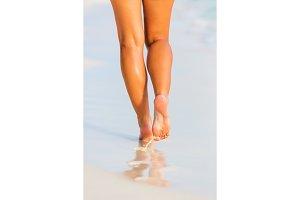Woman legs walking on the beach