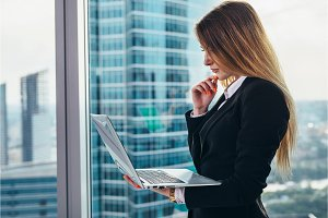 Thoughtful female CEO standing against window in her private office in modern business center holding a laptop reading and thinking