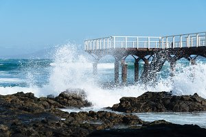 Waves breaking against pier on the beach