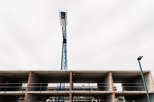 Low angle view of construction crane against cloudy sky