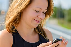 Young cheerful beautiful female using mobile phone