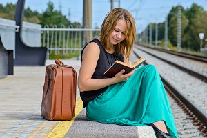 Woman sitting on the station and reading