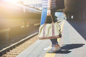 Woman holding a bag at a train station.