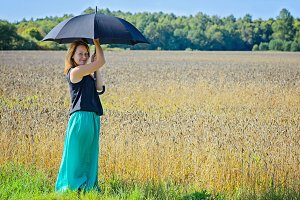 Portrait of woman with umbrella in field