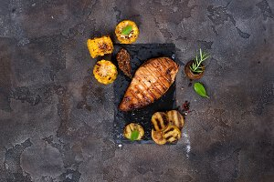 Marinated grilled healthy chicken breasts cooked on a summer BBQ and served with fresh herbs, potatoes and corn