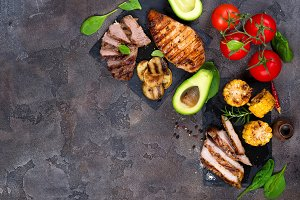 Fresh three types of grilled steak (chicken, pork, beef) on slate plate with herbs, tomato, avocado and grilled potatoes