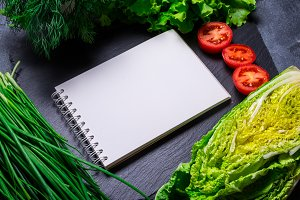 Fresh vegetables and paper notebook