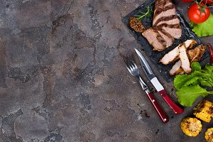 Fresh three types of grilled steak ( pork, beef) on slate plate with herbs, tomato and grilled potatoes