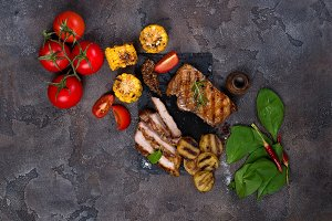 sliced pork steak and grilled vegetables on slate board on stone table.