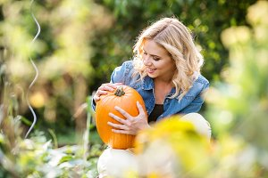 Beautiful young blond woman in her garden harvesting pumpkins