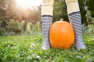 Unrecognizable woman in striped rubber boots with orange pumpkin