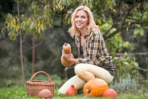 Beautiful young blond woman in her garden harvesting pumpkins