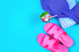 Flip-flops, swimsuit, towel and ice cocktail on a blue pastel background. Rest, travel. Top view. Copy space. Flat lay.