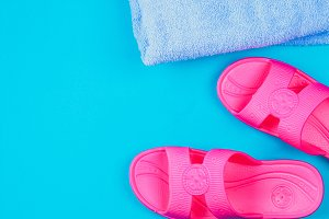 Slippers, towel on a blue pastel background. Rest, travel. Top view. Copy space. Flat lay.