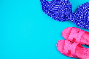 Slippers, swimsuit, towel on a blue pastel background. Rest, travel. Top view. Copy space. Flat lay.