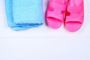 Slippers, towel on a white wooden floor. Rest, travel. Top view. Copy space. Flat lay.